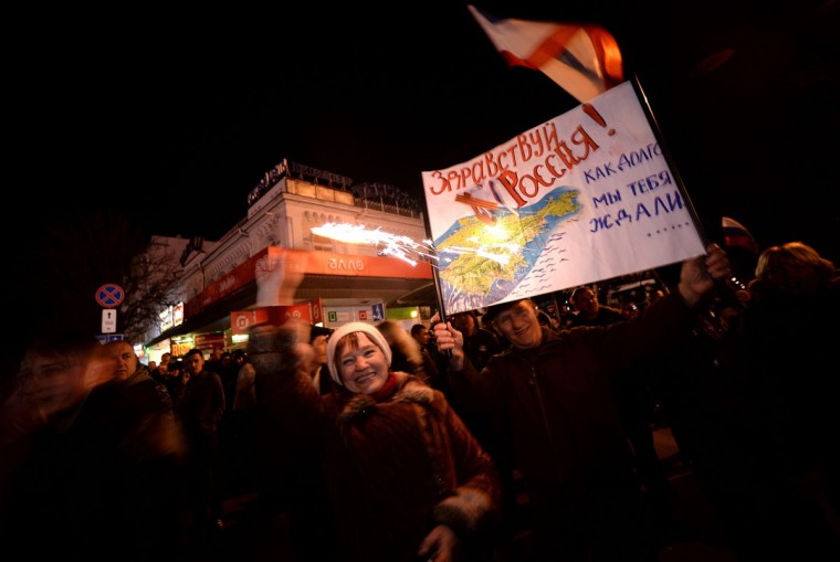 """Pro-Russian Crimeans hold a sign reading """"Hello Russia!"""" as they gather to celebrate in Simferopol's Lenin Square on March 16, 2014 after exit polls showed that about 93 percent of voters in Ukraine's Crimea region supported union with Russia. (Filippo Monteforte/AFP/Getty Images)"""