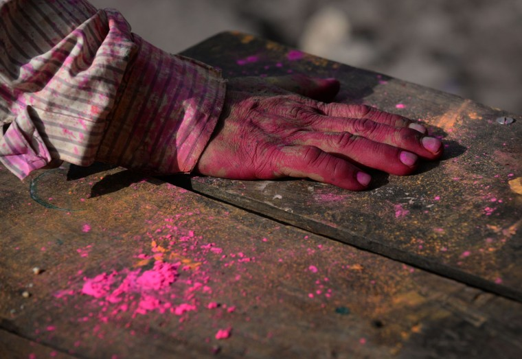 The hand of an Indian laborer is covered in colors as it rests on a table during celebrations for Holi, the Festival of Colors in the old quarters of New Delhi on March 17, 2014. (Sajjad Hussain/AFP/Getty Images)