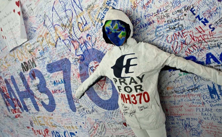 A performer poses in front of messages expressing prayers and well-wishes for passengers onboard missing Malaysia Airlines (MAS) flight MH370 at Kuala Lumpur International Airport in Sepang on March 17. An investigation into the pilots of missing Malaysia Airlines flight 370 intensified on March 17 after officials confirmed that the last words spoken from the cockpit came after a key signalling system was manually disabled.      || CREDIT: MANAN VATSYAYANA - AFP/GETTY IMAGES