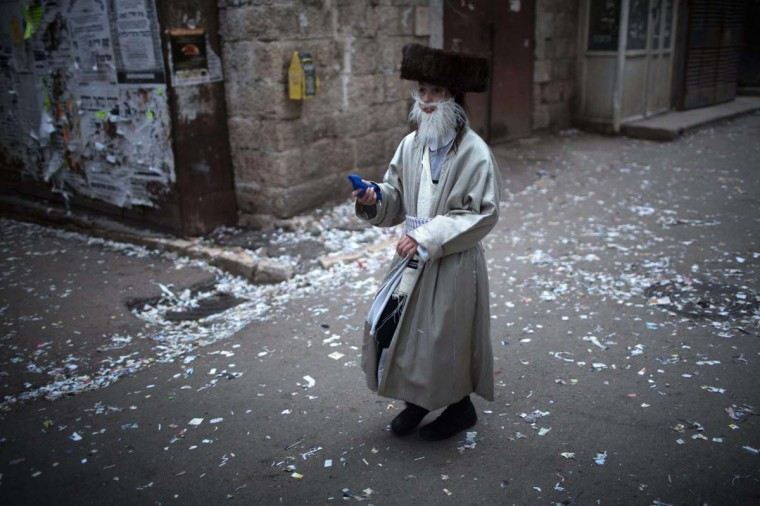 An ultra-Orthodox Jewish boy wearing a costume walks on a trash-strewn street in Jerusalem on March 16, during the feast of Purim. || CREDIT: MENAHEM KAHANA - AFP/GETTY IMAGES
