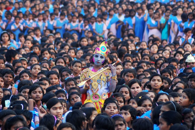 An Indian schoolchild dressed as the Hindu god Krishna and adorned with colored powder stands among other students during celebrations for the spring festival Holi in Bhubaneswar on March 16, 2014. (Asit Kumar/AFP/Getty Images)