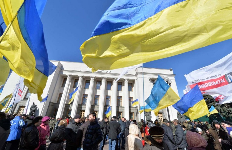 People hold Ukrainian flags as they gather in front of the parliament in Kiev on March 17, 2014. Ukrainian troops will remain in Crimea, the country's defence minister said that day even as media reported the separatist peninsula planned to disband Ukrainian units there. The day before Crimeans voted overwhelmingly to join former political master Russia as tensions soared in the east of the splintered ex-Soviet nation amid the worst East-West crisis since the Cold War.  || CREDIT: SERGEI SUPINSKY - AFP/GETTY IMAGES