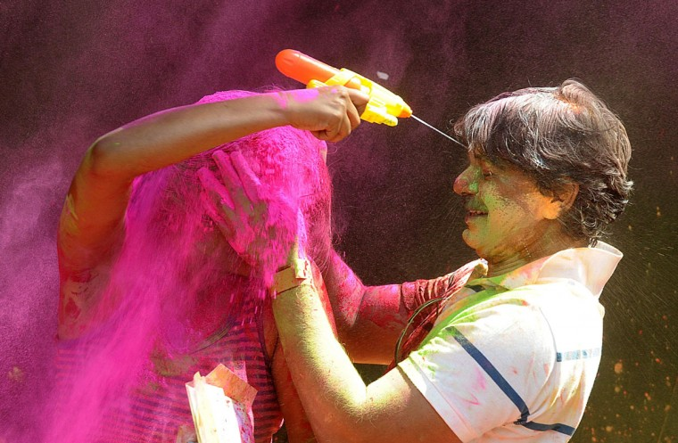 Indian revelers play with colored powder during Holi celebrations in Hyderabad on March 17, 2014. Holi, also called the Festival of Colors, is a popular Hindu spring festival observed in India at the end of the winter season on the last full moon day of the lunar month. (Noah Seelam/AFP/Getty Images)