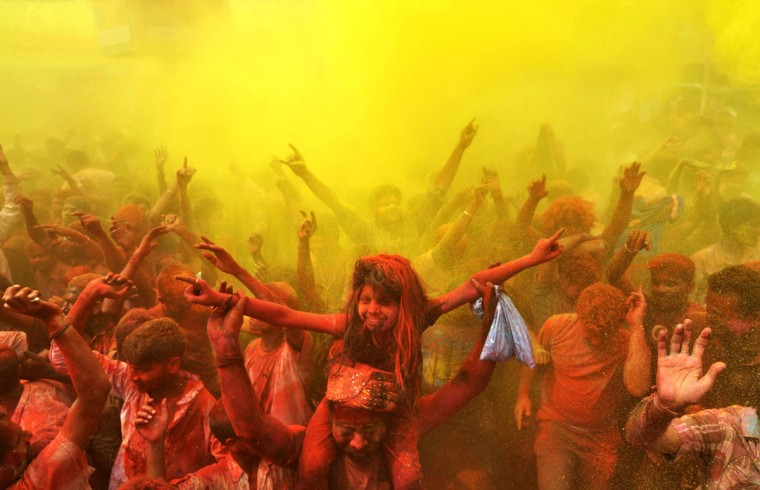 Indian revelers cover each other with colored powder and dance while taking part in Holi festival celebrations in Guwahati on March 17, 2014. Holi, the Festival of Colors, is a popular Hindu spring festival observed in India and Nepal at the end of winter season on the last full moon day of the lunar month. (Biju Boro/AFP/Getty Images)