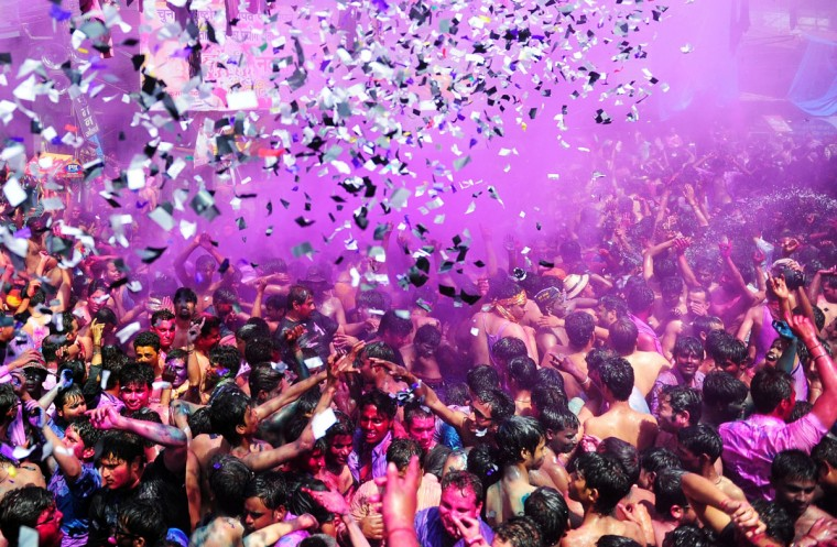 Indian revelers covered in colored powder dance during Holi festival celebrations in Allahabad on March 17, 2014. (Sanjay Kanojia/AFP/Getty Images)