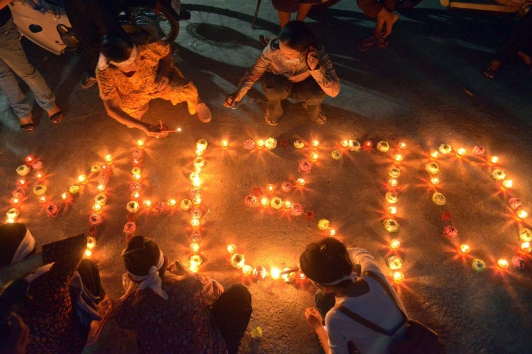 Cambodian residents of a community light candles as they pray for the missing Malaysia Airlines flight MH370 at their village in Phnom Penh on March 17. An investigation into the pilots of missing Malaysia Airlines flight 370 intensified on March 17 after officials confirmed that the last words spoken from the cockpit came after a key signalling system was manually disabled.   || CREDIT: TANG CHHIN SOTHY - AFP/GETTY IMAGES
