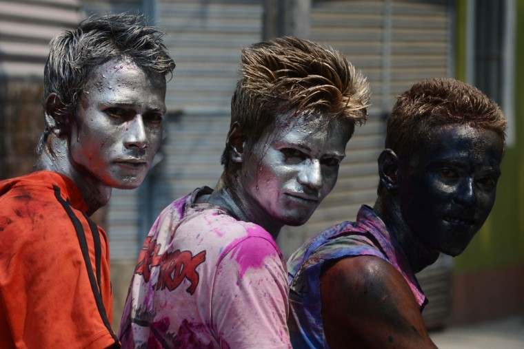 Indian revelers painted in metallic paints pose for a photograph during Holi festival celebrations in Siliguri on March 17, 2014. (Diptendu Dutta/AFP/Getty Images)