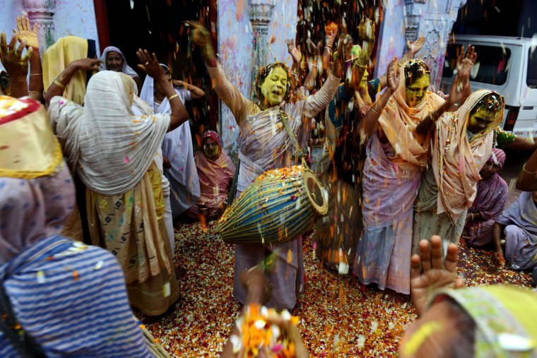 Indian widows throw colored powder and flower petals as they take part in Holi celebrations at an ashram in Vrindavan on March 17, 2014. (Chandan Khanna/AFP/Getty Images)
