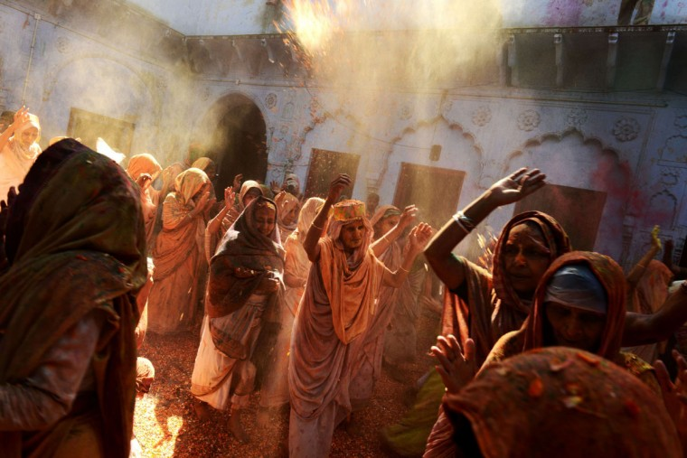 Indian widows throw colored powder and flower petals as they dance during Holi celebrations at an ashram in Vrindavan on March 17, 2014. Breaking centuries-old tradition, widows living in the holy city of Vrindavan celebrated the spring color festival of Holi at Meera Sahabhagini Sadan in Vrindavan. As per Indian tradition, widows are considered social outcasts and refrain from celebrating Holi. (Chandan Khanna/AFP/Getty Images)
