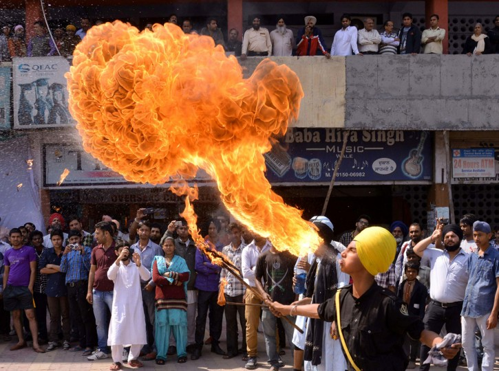 Indian Sikh youths perform fire-breathing as they demonstrate Gatka martial arts skills while welcoming unseen Bharatiya Janata Party (BJP) senior leader and candidate for Amritsar's parliamentary seat Arun Jaitley to an event in Amritsar on March 18, 2014. India, the world's biggest democracy, announced the start of national elections on April 7 that are expected to bring Hindu nationalist Narendra Modi to power on a platform of economic revival. (Narinder Nanu/AFP/Getty Images)