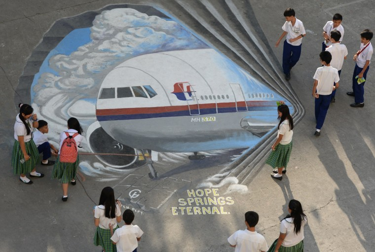 Students stand next to a giant mural featuring missing Malaysia Airlines flight MH370 displayed on the grounds of their school in Manila's financial district of Makati on March 18, 2014, created as part of solidarity action by concerned artists for the passengers and crew of the missing plane. Three million people around the world have joined an effort led by a satellite operator to locate the missing Malaysia Airlines plane, in what may be the largest crowdsourcing project of its kind. The plane went missing early on March 8 with 239 passengers and crew aboard, spawning a massive international search across Southeast Asia and the Indian Ocean that has turned up no trace of wreckage. (Ted Aljibe/AFP/Getty Images)