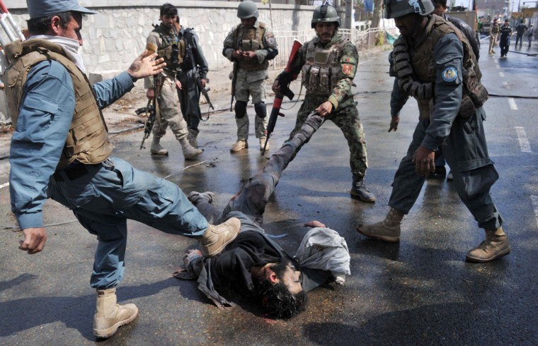 Afghan security personnel drag and kick the body of a militant at the scene of an attack on a police station in Jalalabad on March 20, 2014. At least six Taliban suicide attackers stormed a police station in the centre of the eastern Afghan city of Jalalabad, killing three people in a major assault ahead of the presidential election.The target of the complex assault was a police station close to the governor's house in Jalalabad city, which has been the scene of repeated militant attacks in recent years. (Noorullah Shirzada/AFP/Getty Images)