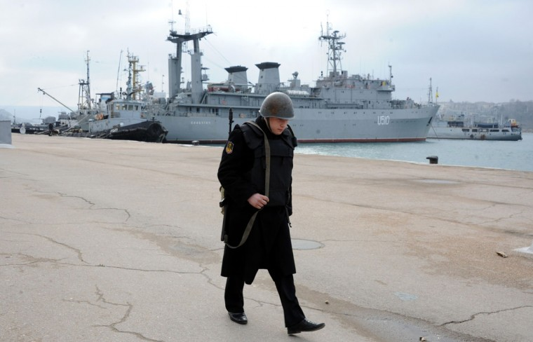 A Russian sailor walks in front of the Slavutych Ukrainian navy ship moored in Sevastopol bay on March 20, 2014. Ukraine's ambassador to the United Nations in Geneva warned Thursday there were signs that Moscow was preparing to launch a large-scale assault in southern and eastern parts of his crisis-hit country. (Viktor Drachev/AFP/Getty Images)
