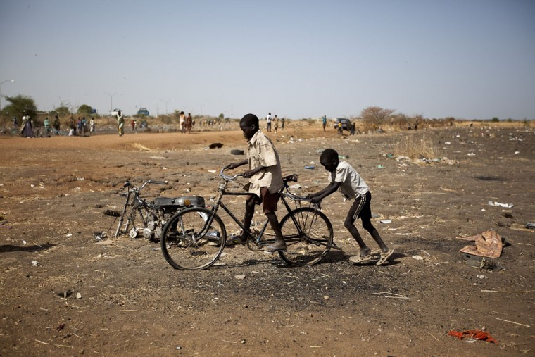 Two boys play with a broken bicycle near the United Nations Mission in South Sudan (UNMISS) base in Malakal on March 20, 2014. Malakal is a key city in an oil-producing region in the country's northeast, 497km north of Juba. South Sudan's government has been at war with rebel groups since December 15, when a clash between troops loyal to President Salva Kiir and those loyal to sacked vice president Riek Machar snowballed into full-scale fighting. Thousands have died in more than three months fo fighting and over 930,000 civilians have fled their homes, including over a quarter of a million leaving for neighbouring nations as refugees, according to the United Nations. (Ivan Lieman/AFP/Getty Images)