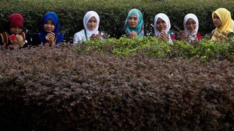 "Young Malaysian Muslim girls offer Friday prayers as they sit outside the Putra mosque in Putrajaya on March 21, 2014. Surveillance aircraft scoured a remote and stormy section of the Indian Ocean on March 20 for a pair of floating objects that Australia and Malaysia guardedly called a ""credible"" lead in the 12-day-old hunt for the missing passenger jet. (Manan Vatsyayana/AFP/Getty Images)"