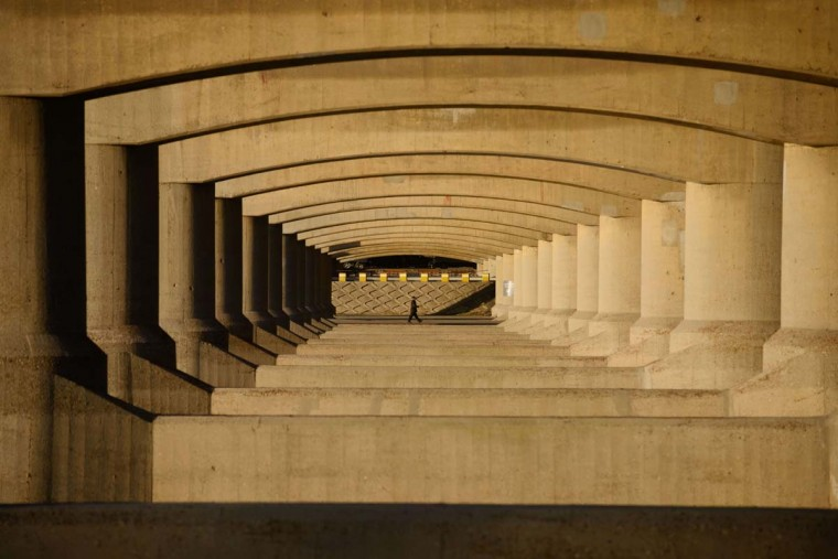 A pedestrian passes beneath a road bridge in Seoul on March 21, 2014. Nineteen bridges over the Han River link Seoul to its southern suburbs.(Ed Jones/AFP/Getty Images)