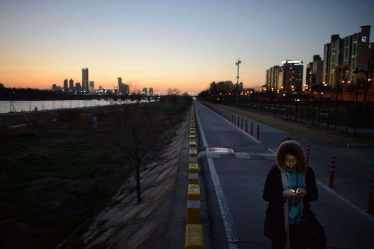 A woman uses a smartphone before the city skyline in Seoul at dusk on March 21, 2014. South Korea, already one of the most wired countries on earth, announced in January 2014 a 1.6 trillion won (1.5 billion USD) plan to roll out a next-generation 5G wireless service quick enough to download full-length films in a second. (Ed Jones/AFP/Getty Images)