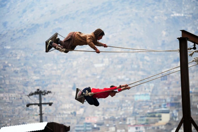Afghan boys take flight on swings at a fair set up in a field near the Sahki Shrine during Nowruz festivities which marks the Afghan New Year in Kabul on March 21, 2014. Nowruz, one of the biggest festivals of the war-scarred nation, marks the first day of spring and the beginning of the year in the Persian calendar. Parents with their children celebrate the New Year by participating in the fair set up near the shrine. (Roberto Schmidt/AFP/Getty Images)