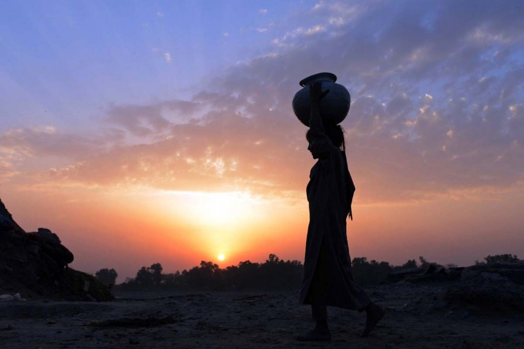 A young Pakistani girl carries a water pot over her head as she heads for home during sunset on the outskirts of Lahore on March 21, 2014, on the eve of World Water Day. International World Water Day is held annually on March 22 to focus global attention on the importance of water and advocating for the sustainable management of our water resources. (Arif Ali/AFP/Getty Images)