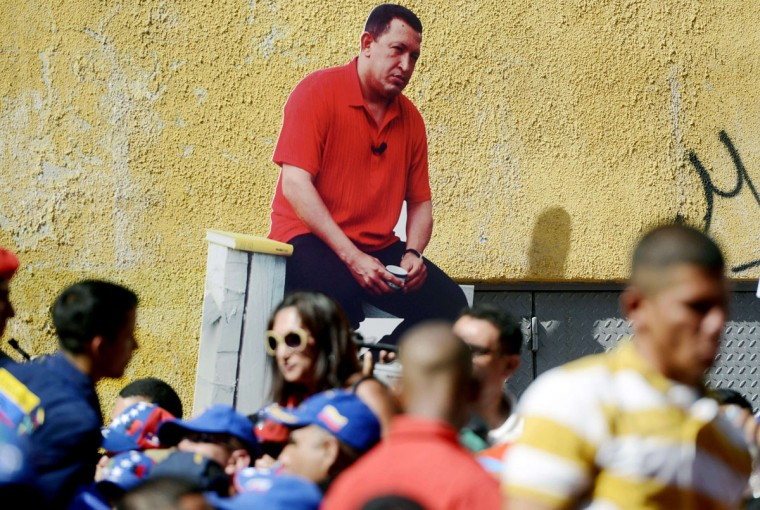 A supporter of Venezuelan President Nicolas Maduro holds an image of the late president Hugo Chavez (left background) during a mass meeting in Caracas on March 22, 2014. (Leo Ramirez/AFP/Getty Images)