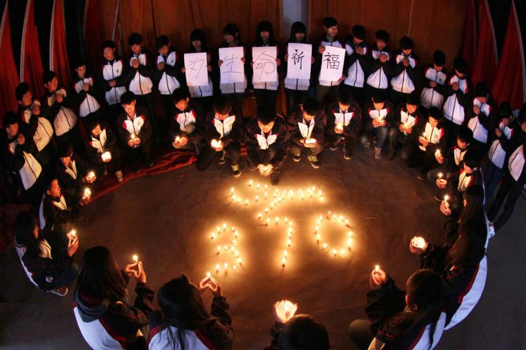 High school students hold candles during a vigil for passengers of the missing Malaysia Airline flight MH370 in Lianyungang, east China's Jiangsu province on March 25, 2014. Scores of angry relatives of the Chinese passengers aboard Flight MH370 set out on a protest march to the Malaysian embassy in Beijing on March 25 to demand more answers about the crashed plane's fate. (AFP/Getty Images)