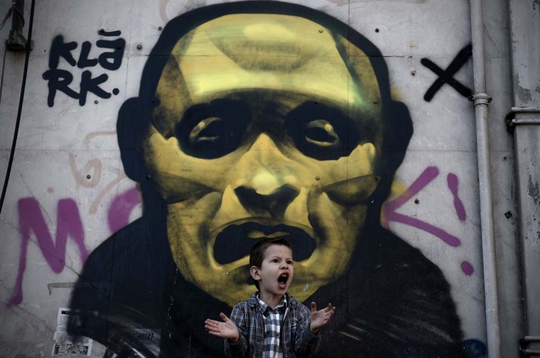 A young boy shouts in front of a street painting as he attends a military parade in central Athens during a ceremony marking the Greek Independence Day on March 25, 2014. (Aris Messini/AFP/Getty Images)