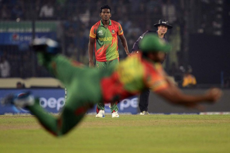Bangladesh cricketer Al-Amin Hossain (C) watches as his teammate Tamim Iqbal tries take a catch to dismiss West Indies batsman Dwayne Bravo during the ICC World Twenty20 tournament Group 2 cricket match between Bangladesh and West Indies at The Sher-e-Bangla National Cricket Stadium in Dhaka on March 25, 2014. (Munir uz Zaman/AFP/Getty Images)