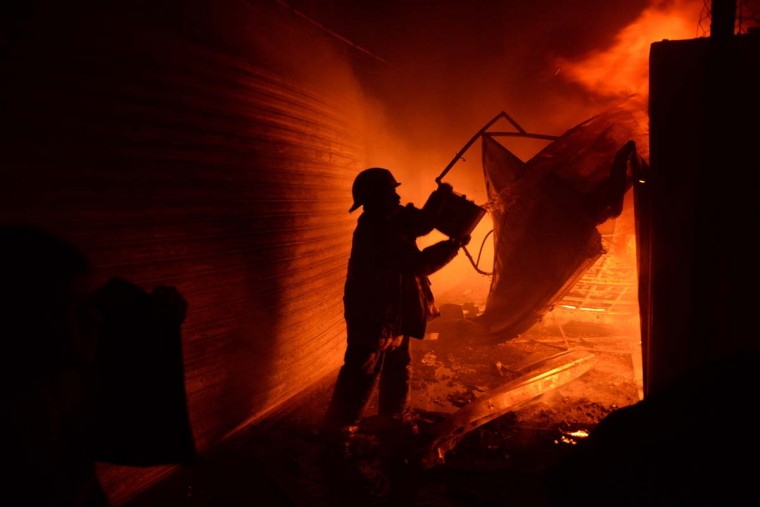 A firegfighter tries to douse a fire in La Terminal market on March 25, 2014 in Guatemala City. The disaster left four injured, 50 intoxicated and at least 400 stalls destroyed. (Johan Ordonez/AFP/Getty Images)