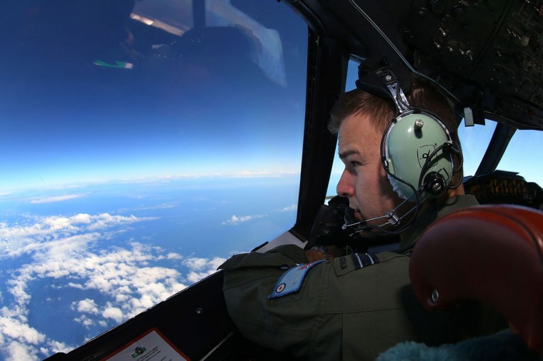 RAAF Flight Lieutenant Russell Adams looks out from the cockpit of a AP-3C Orion during a search mission for missing Malaysia Airline flight MH370 in the Southern Indian Ocean on March 26, 2014. The race to find wreckage from flight MH370 took on new urgency on March 27, 2014, ahead of forecast bad weather after satellite images of more than 100 floating objects sparked fresh hopes of a breakthrough. (Paul Kane/AFP/Getty Images)