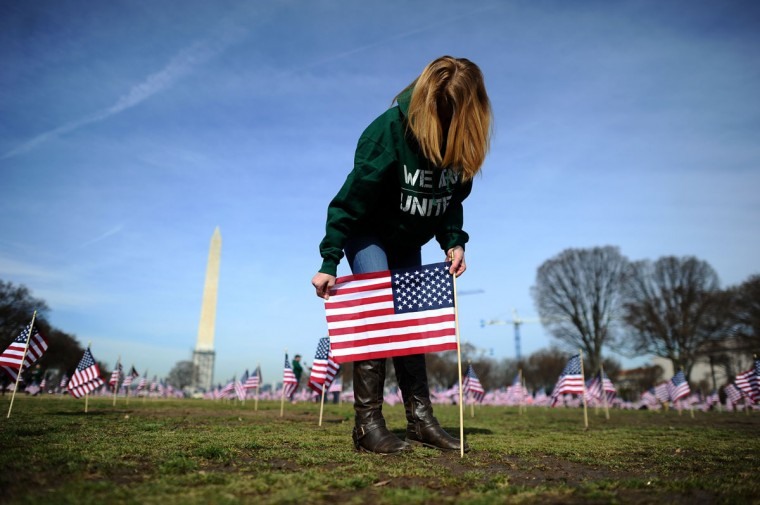 "A war veteran helps set up 1,892 American flags on the National Mall in Washington, DC, on March 27, 2014. The Iraq and Afghanistan veterans installed the flags to represent the 1,892 veterans and service members who committed suicide this year as part of the ""We've Got Your Back: IAVA's Campaign to Combat Suicide."" (Jewel Samad/AFP/Getty Images)"