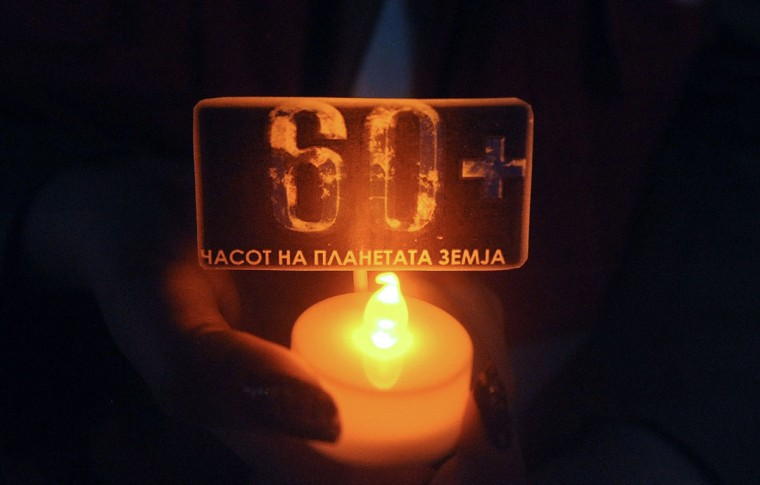 "An activist of the Red Cross NGO holds a candle with the number ""60+"", during the ""Earth Hour"" event at Skopje main square, on March 29, 2014. (ROBERT ATANASOVSKI/AFP/Getty Images)"