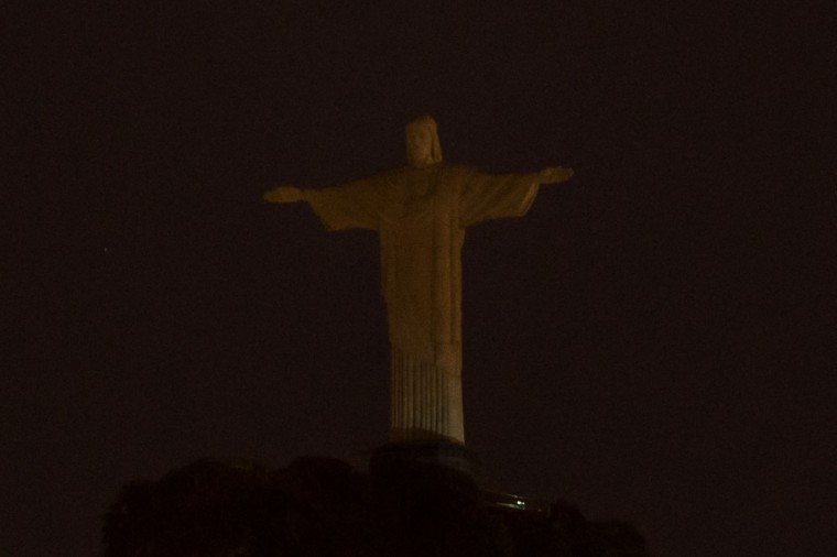 "The statue of Christ the Redeemer is seen without light during the annual ""Earth Hour"" atop Corcovado Hill in Rio de Janeiro, Brazil, on March 29, 2014. (YASUYOSHI CHIBA/AFP/Getty Images)"