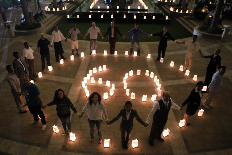 "Employees of the Jumeirah Messilah Beach Hotel surround candles forming the number ""60"" during the Earth Hour on March 30, 2014 in Kuwait city. (YASSER AL-ZAYYAT/AFP/Getty Images)"