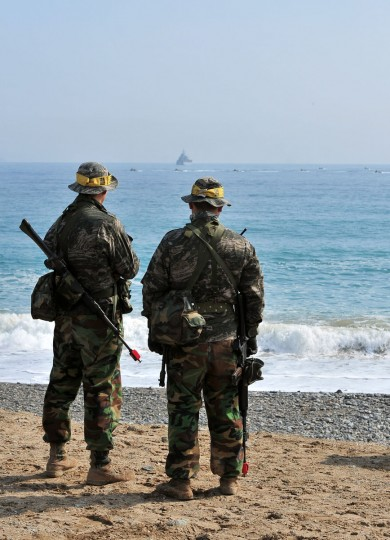South Korean Marines stand on a beach as amphibious assault vehicles (in background) head toward the seashore during a joint landing operation with U.S. marines in Pohang. (JUNG YEON-JE/AFP/Getty Images)