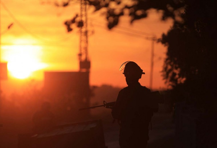 A member of Israeli security forces stands at sunset during clashes with Palestinians following a protest against the expansion of the nearby Israeli settlement of Ofra on March 28, 2014 in the West Bank village of Silwad, north of Ramallah. (Abbas Momani/AFP Getty Images)