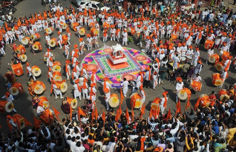 Indian drummers in traditional attire play on around a rangoli design during a procession celebrating 'Gudi Padwa' or the Maharashtrian new year in Mumbai on March 31, 2014. Gudi Padwa is the Hindu new year in the Indian state of Maharashtra and falls on the first day of the month of Chaitra according to the lunar calendar. It is celebrated by dancing and singing with every member of the family wearing new clothes in traditional attire. The day traditionally starts with the cleaning ritual, in which the house is fully cleaned (in case of villages, it is then covered with fresh cow-dung). Women and children draw andpaint intricate rangoli designs using vibrant colors, in keeping with the spirit of the festival, on their doorsteps. (Indranil Mukherjee/AFP/Getty Images)