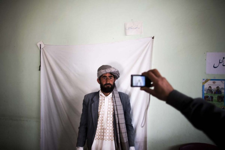 An Afghan election employee takes a picture of a resident to issue his voter card for the upcoming presidential election at a voter registration centre in the northwestern city of Herat on March 31, 2014. Crowds queued up outside voter registration centres in Afghanistan and presidential candidates held large outdoor rallies for supporters five days ahead of elections that have been shaken by Taliban attacks. The vote, which will choose a successor to President Hamid Karzai, comes as US-led foreign troops withdraw after 13 years of fighting the fierce Islamist insurgency raging across the south and east of the country. (Berhouz Mehri/AFP/Getty Images)