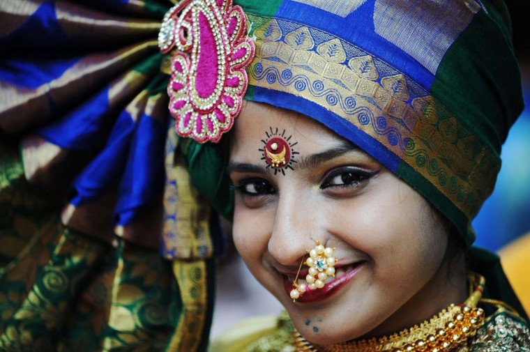 An Indian resident wearing traditional jewelery takes part in a procession celebrating 'Gudi Padwa' or the Maharashtrian new year in Mumbai on March 31, 2014. Gudi Padwa is the Hindu new year in the Indian state of Maharashtra and falls on the first day of the month of Chaitra according to the lunar calendar. It is celebrated by dancing and singing with every member of the family wearing new clothes in traditional attire. The day traditionally starts with the cleaning ritual, in which the house is fully cleaned (in case of villages, it is then covered with fresh cow-dung). Women and children draw andpaint intricate rangoli designs using vibrant colors, in keeping with the spirit of the festival, on their doorsteps. (Indranil Mukherjee/AFP/Getty Images)