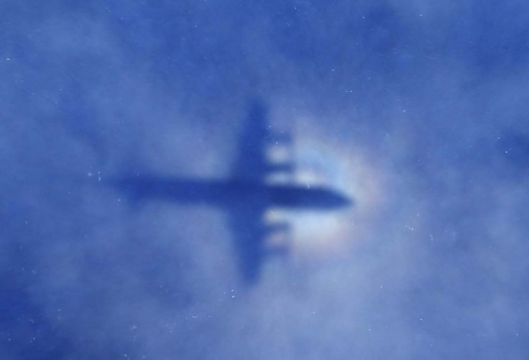 "This shadow of a Royal New Zealand Air Force P3 Orion aircraft is seen on low cloud cover while it searches for missing Malaysia Airlines flight MH370, over the Indian Ocean on March 31, 2014. No time limit will be imposed on the search for MH370 because the world deserves to know what happened, Australian Prime MinisterTony Abbott said, as a ship equipped to locate the plane's ""black box"" prepared to set sail. (Rob Griffith/AFP/Getty Images)"