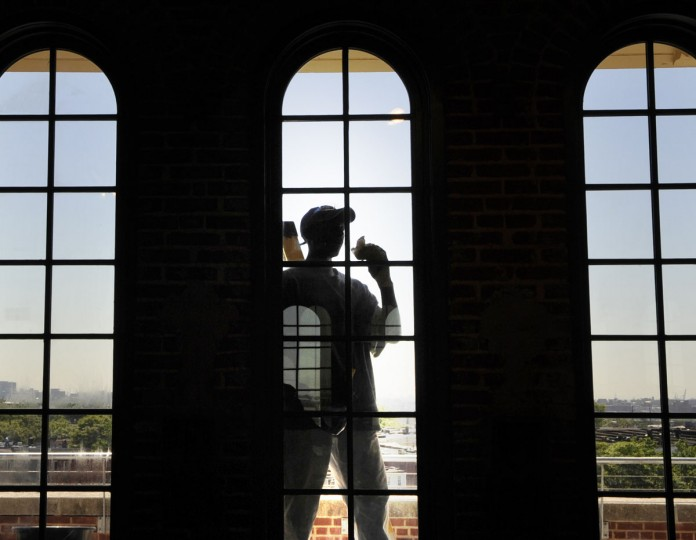 Kenneth W. Lewis, a laborer from the neighborhood, cleans windows of a conference room that looks out east towards the Key Bridge. (Jed Kirschbaum/Baltimore Sun)