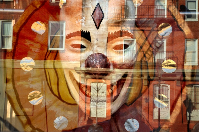 The reflection of the 700 block of North Howard St. melds with one of the antique oversized clown masks in the display windows of The A.T. Jones & Sons costume company. (Amy Davis / Baltimore Sun)
