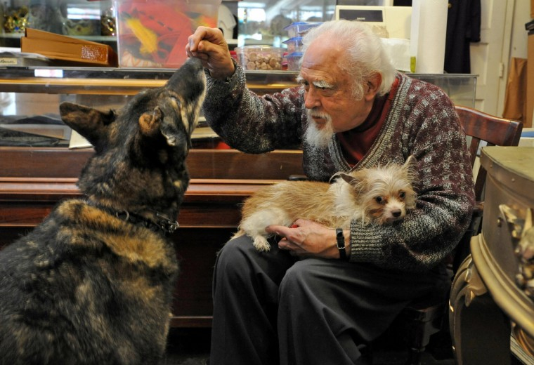 A.T. Jones & Sons costume shop owner, George Goebel, 81, spends time during his lunch break with his German Shepherd, Norman, left, and Tazwell, who comes to the costume shop every day with his owner, employee John Bernatitus. Goebel also had a renowned career as a magician. (Amy Davis / Baltimore Sun)