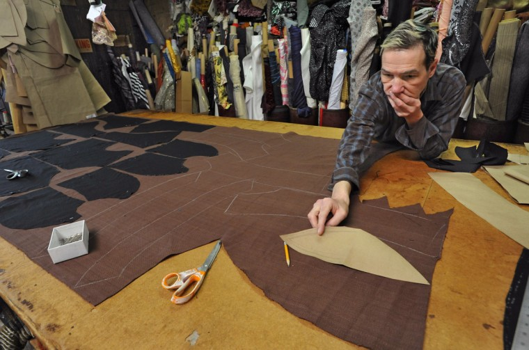 Costumer John Bernatitus places custom pattern pieces on fabric for a jacket design. All of the costumes start the old-fashioned way, from a bolt of fabric. (Amy Davis / Baltimore Sun)