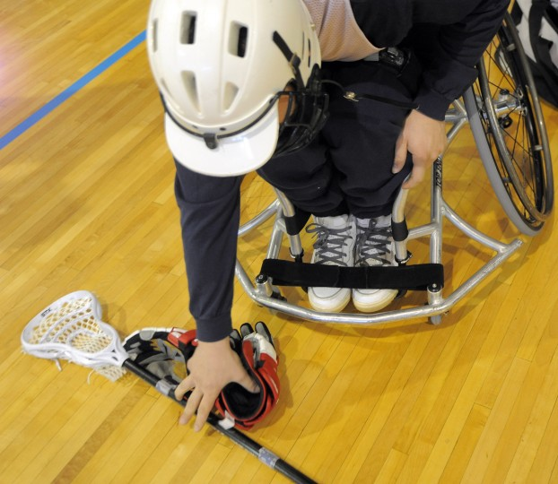 Anthony Caparella, 26, Burtonsville, picks up gloves and a lacrosse stick before the Wheelchair Lacrosse Clinic at Johns Hopkins University. (Kim Hairston/Baltimore Sun)