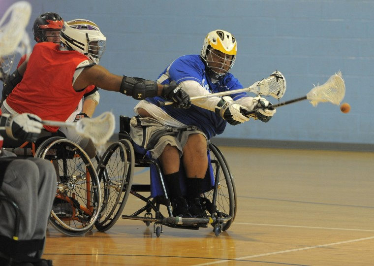 Left to right, Carlton Coleman, 57, Clarksville, forces Larry Toler, 55, Baltimore, to loose the ball in a scrimmage of a Wheelchair Lacrosse Clinic at Johns Hopkins University. (Kim Hairston/Baltimore Sun)