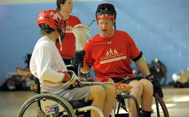 Left to right, Ryan Beale, 24, Suffolk, VA, talks with Mark Flounlacker, Ocean Pines, founder of FreeState Wheelchair Lacrosse, during skills building at a Wheelchair Lacrosse Clinic. Kennedy Krieger International Center for Spinal Cord Injury partners with FreeState to put on the clinic in a Johns Hopkins University gym. Beale is wearing the helmet he used when he played for Lynchburg College. He broke his neck in 2009 in an accident. (Kim Hairston/Baltimore Sun)