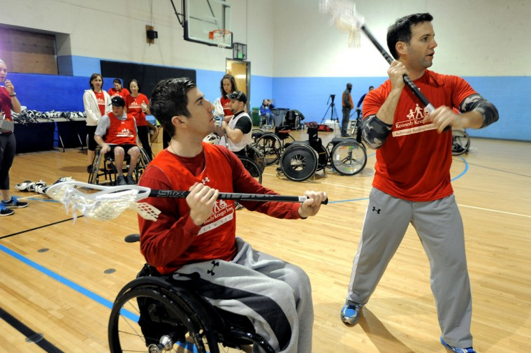Mike Fritschner, 23, Fells Point, watches as Jason Myers gives instruction in how to hold and throw with a lacrosse stick. Fritschner, has been in a wheelchair since 2006 with surfer's myelopathy and is having his first experience with lacrosse. Myers has played the sport and is volunteering to teach others. (Kim Hairston/Baltimore Sun)
