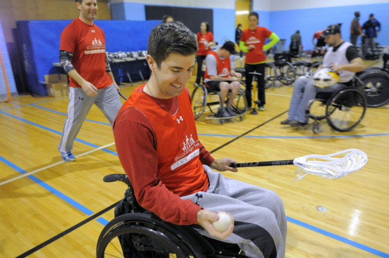 Mike Fritschner, 23, Fells Point, checks out a lacrosse ball as he has his first experience with the sport at a Wheelchair Lacrosse Clinic hosted by Kennedy Krieger International Center for Spinal Cord Injury in connection with FreeState Wheelchair Lacrosse. (Kim Hairston/Baltimore Sun)