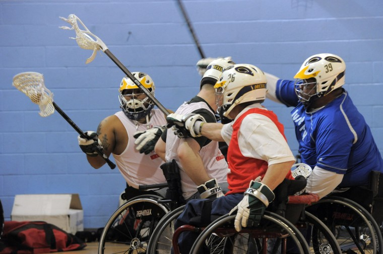 Left to right. Harsh Thakkar, 28, Silver Spring, keeps control of the ball as, second from right, Ernie Butler, 60, director of Sports and Recreation for Paralyzed Veterans of America, and, right, Larry Toler, 55, Baltimore, try to knock it from his stick. (Kim Hairston/Baltimore Sun)