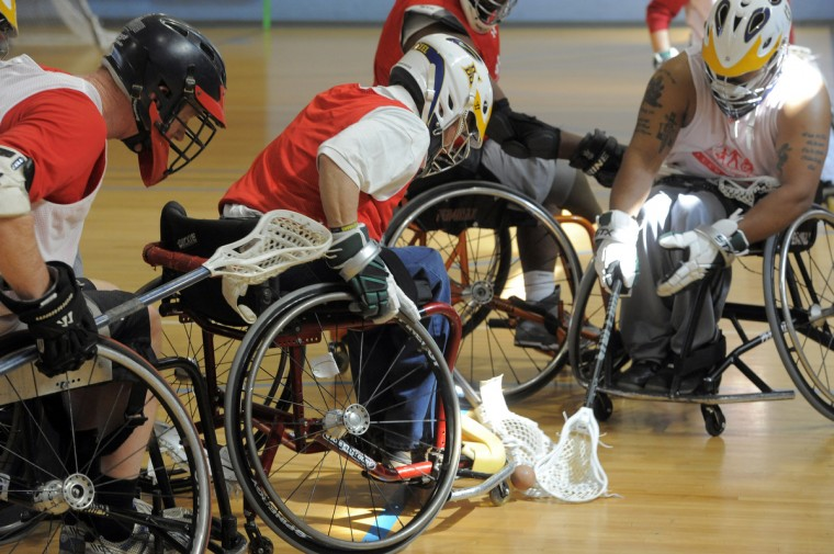 Left to right, Mark Flounlacker, Ocean Pines, founder of FreeState Wheelchair Lacrosse watches as Ernie Butler, 60, director of Sports and Recreation for Paralyzed Veterans of America and Harsh Thakkar, 28, Silver Spring, try to pick up a loose ball. (Kim Hairston/Baltimore Sun)